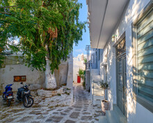 Beautiful Traditional Narrow Cobbled Streets Of Greek Island Towns. Whitewashed Houses, Scooters, Flower Pots, Balconies, Stairs. Mykonos, Greece