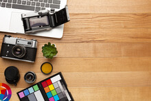 Photographer's Desk Made Of Wood With A Camera And Palettes.