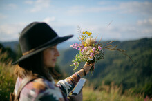 Woman Traveler In Hat Holding Bouquet Of Wildflowers On Background Of Mountain Hills And Sky. Travel