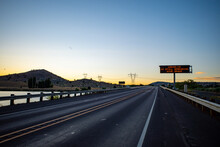 A Highway Sign Warns About Covid-19 During The Pandemic On A Deserted Freeway Road