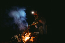 An Older Man 55-70 Years Old Places A Log On A Campfire At Night