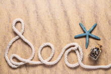 Sea Spelled Out With Nautical Rope With A Blue Starfish And Small Glass Bottle Of Seashells On A Beach Sand Background