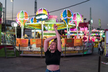 Chica Rubia Guapa Posando Delante De Atracciones De Globos Aerostáticos En Zona De Atracciones De Una Feria