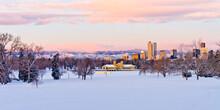Downtown Denver Skyline From City Park At Dawn On A Cold January Morning With Brightly Lit Pink And Purple Clouds Over The Foothills And The City Park Pavilion In The Foreground With A Snow Covered Pa