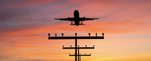 Silhouette Of A Plane Landing At The Airport Against The Background Of Sunset