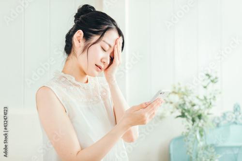 Photo スマホを見て悩む女性(体調不良)