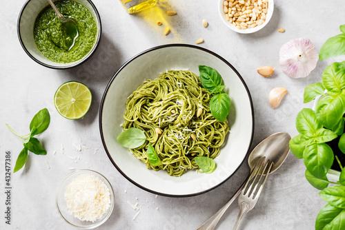 Fototapeta Pasta spaghetti with pesto sauce and fresh basil leaves in grey bowl. Light grey background.Top view. obraz