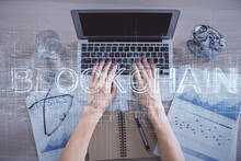 Double Exposure Of Woman Hands Working On Computer And Blockchain Theme Hologram Drawing. Top View. Bitcoin Cryptocurrency Concept.