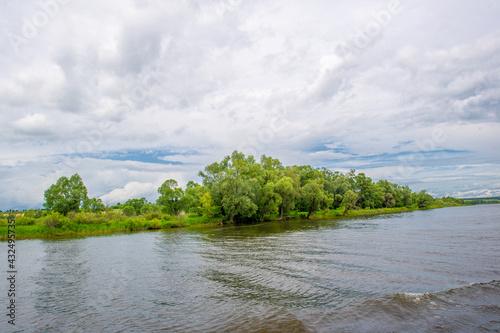 Fotografia summer photo, powerful thunderclouds, blue sky, dark sharp water, tourist walk a