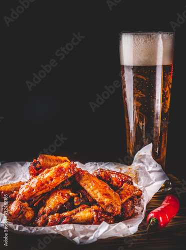 Fotografie, Obraz glass of fresh beer and fried chicken wings on wooden table on black background