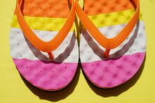 Closeup Colored Beach Flip Flops On A Sunny Yellow Table.
