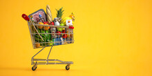 Shopping Cart Full Of Food On Yellow Background. Grocery And Food Store Concept.