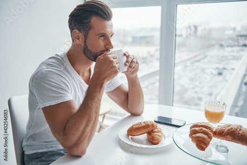 Handsome young man enjoying hot coffee  - fototapety na wymiar