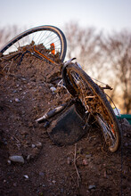 Old Bike That Someone Throwed Away Is Laying In A Pile Of Soil In The Nature