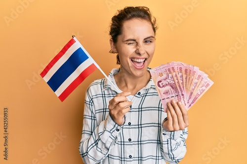 Canvas Print Young brunette woman holding thailand flag and baht banknotes winking looking at the camera with sexy expression, cheerful and happy face