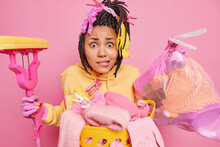 Photo Of Desperate Nervous African American Woman Carries Trash Bag And Mop Puzzled To See Mess And Chaos At Home Supplies House Cleaning Stands Near Laundry Basket Isolated On Pink Studio Wall
