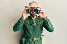 Handsome Man With Beard Wearing Explorer Hat Looking Through Binoculars Skeptic And Nervous, Frowning Upset Because Of Problem. Negative Person.