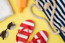 Top View Photo Of White Towel Orange Sunscreen Bottle Beach Bag Striped Flip-flops And Sunglasses On Isolated Pastel Yellow Background