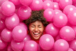 Leinwandbild Motiv Pretty overjoyed young woman has curly hair foolishes around smiles broadly with white teeth keeps eyes closed sticks out head through small pink balloons. Cheerful ethnic female enjoys party