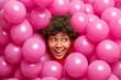 Leinwandbild Motiv Beautiful happy curly dark skinned woman sticks head through heap of pink inflated balloons smiles joyfully looks away has festive mood enjoys party celebration. Holidays and people concept.