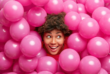 Beautiful Happy Curly Dark Skinned Woman Sticks Head Through Heap Of Pink Inflated Balloons Smiles Joyfully Looks Away Has Festive Mood Enjoys Party Celebration. Holidays And People Concept.