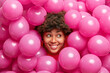 Leinwandbild Motiv Happy cute young African American woman with curly bushy hair smiles broadly looks right has festive mood poses around inflated helium pink balloons expresses positive emotions. Holiday decor.