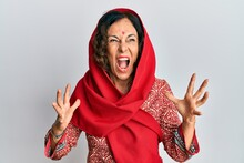 Middle Age Hispanic Woman Wearing Tradition Sherwani Saree Clothes Crazy And Mad Shouting And Yelling With Aggressive Expression And Arms Raised. Frustration Concept.
