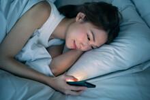 ベッドで寝ながらスマートフォンを見る女性