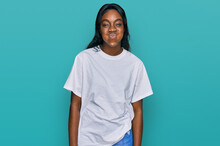 Young African American Woman Wearing Casual White T Shirt Puffing Cheeks With Funny Face. Mouth Inflated With Air, Crazy Expression.