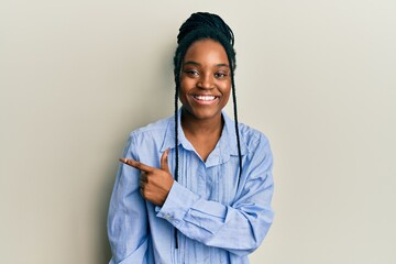 African american woman with braided hair wearing casual blue shirt smiling cheerful pointing with hand and finger up to the side