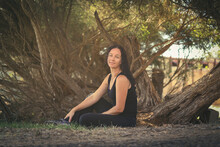 Brunette Woman Wearing Black Sitting On Ground With Australian Paperbark Tree In Background