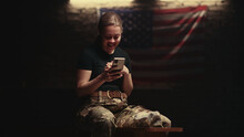 Delighted Female Soldier Sitting On Bench And Making Video Call