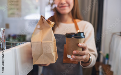 Fototapeta Closeup image of a waitress holding and serving paper cup of coffee and takeaway food in paper bag to customer in a shop obraz