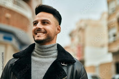 Vászonkép Young arab man smiling happy standing at the city.