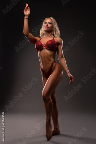 Powerful blond female model with glittering bikini in dark - fototapety na wymiar
