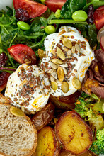 Appetizing And Hearty Breakfast With Poached Egg, Potatoes, Bacon, Grapes, Mix Salad And Rye Bread In A White Bowl On A Wooden Background
