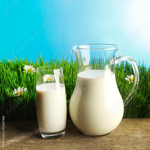 Obraz Glass of milk and jar on flower meadow - fototapety do salonu