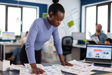 Black businesswoman checking work of multiethnic colleagues in startup agency. Diverse team of business people analyzing company financial reports from computer. Start up Successful corporate