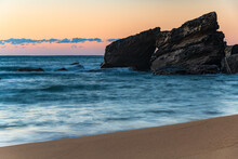 Sunrise At The Seaside With Soft Orange Pink Sky And Large Rocky Outcrop