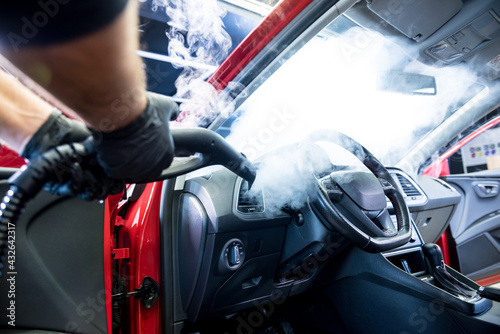 Car service worker cleans interiror with steam cleaner - fototapety na wymiar