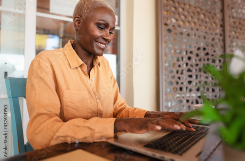 Fotografia African woman working on laptop in bar restaurant - Afro female typing on comput