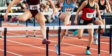 Four Girls Running In An Indoor Hurdle Race