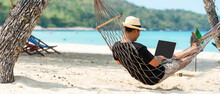 Lifestyle Freelance Man Using Laptop Working And Relax On The Beach. Asian People On Hammock Success And Together Your Work Pastime And Meeting Conference On Internet In Holiday