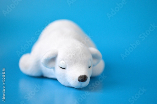 Fotografiet Figurine in the form of a sleeping polar bear on a blue background