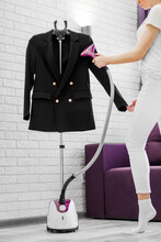 The Girl Holds In Her Hand A Steamer For Clothes For Black Jacket That Hang On A Hanger