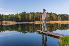 Man Stands On A Wooden Pier Near Spring Forest On A Calm Lake In Ukraine. Nature And Travel Concept