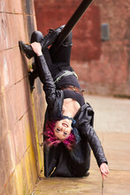 Alternative Gothic Woman Model Hanging Upside Down On A Brick Wall