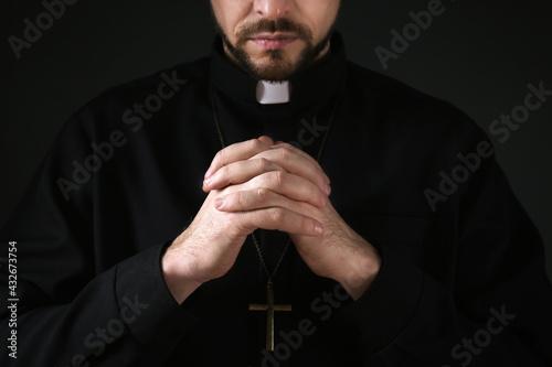 Billede på lærred Priest in cassock praying on dark background, closeup
