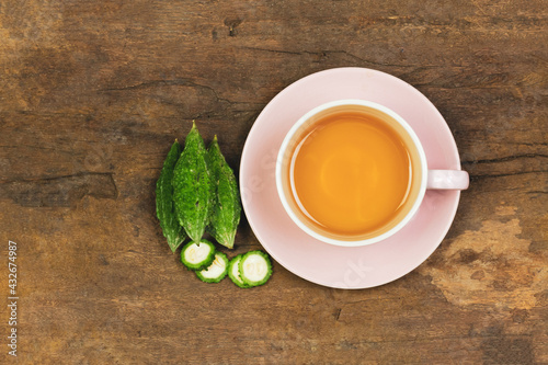 Bitter gourd or bitter melon tea in ceramic cup on wooden background, top view. Scientific name is Momordica charantia. As a whole food and herbs for treating diseases. - fototapety na wymiar