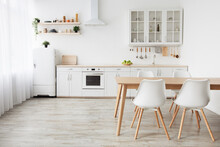 Scandinavian Home Interior. White Kitchen Furniture With Utensils And Dinner Table With Chairs, Empty Space